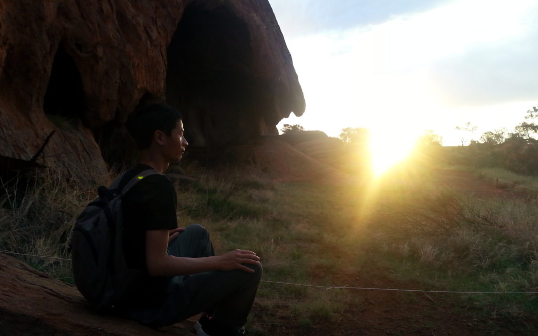 tim chan sitting and meditating on rock in uluru