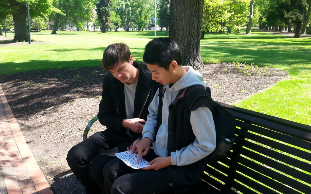tim chan sitting on a park bench with support worker ruben